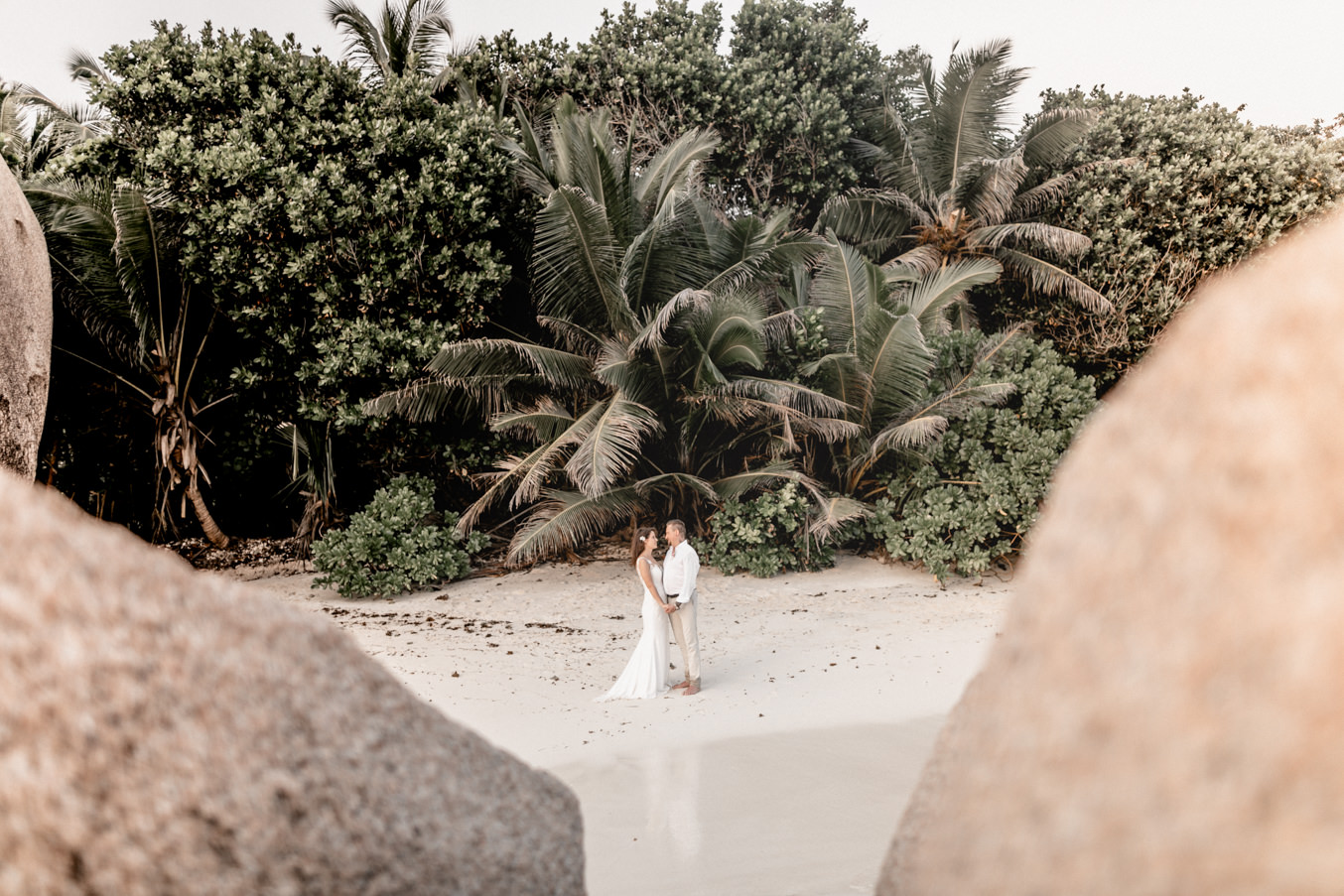 Destination Wedding photographer with bridal couple at the beach of La Digue