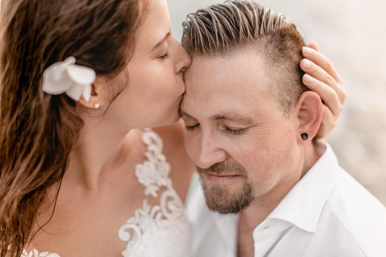 Brautpaar küsst sich bei Hochzeit am Strand auf den Seychellen