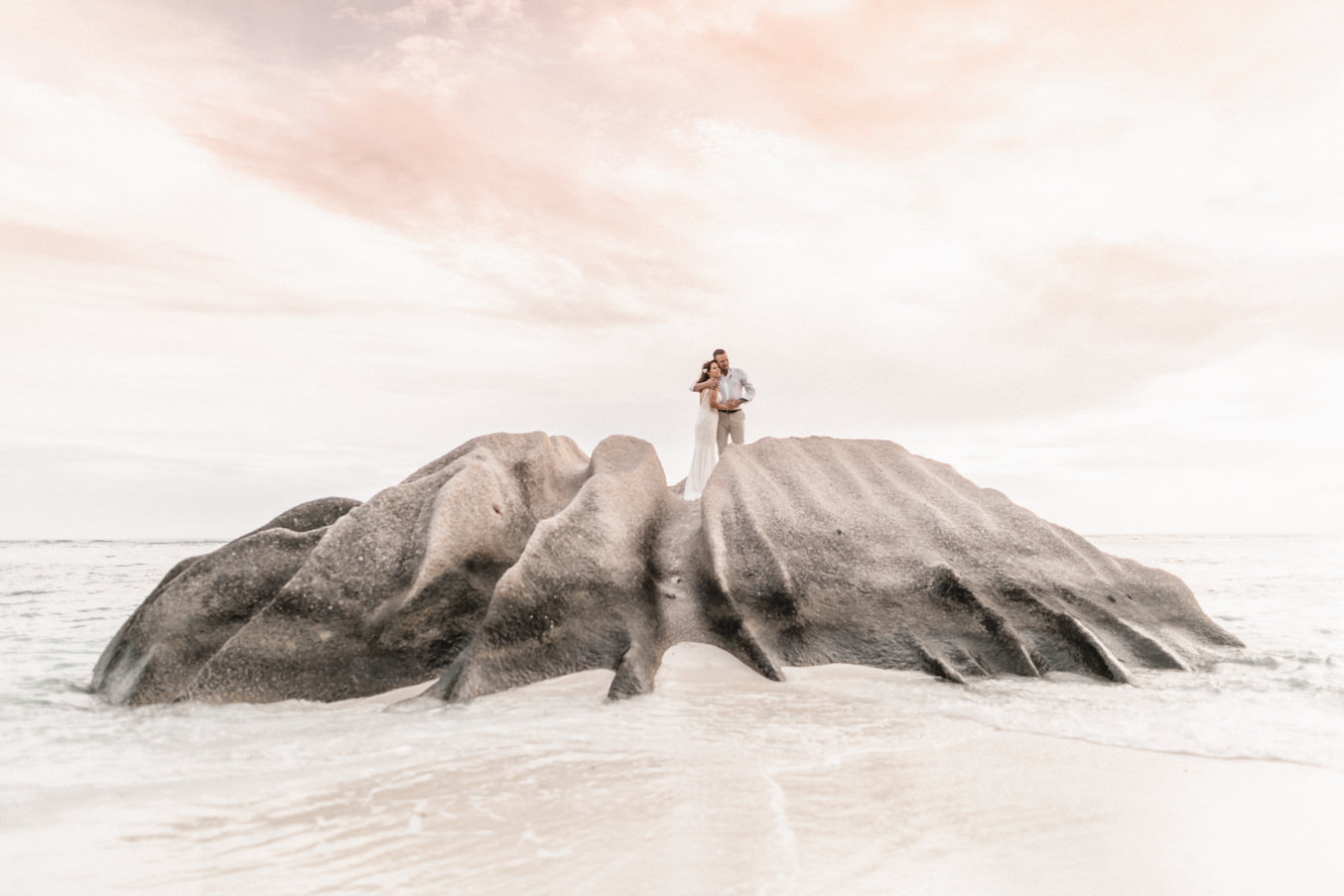Bridal couple with wedding photographer photoshooting at the beach of la Digue in Seychelles